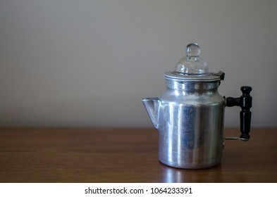 Vintage retro percolator coffee pot small on wooden table room for text background
