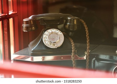 Vintage retro phone in traditional british red booth close up