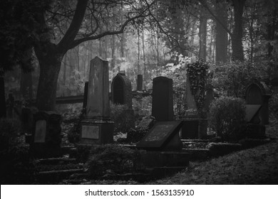 Vintage, retro photo of old graves and tombstones in an ancient cemetery. Grainy, noisy, artistic monochrome image. Halloween, all saints concept.