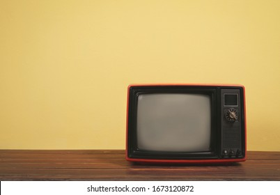 Vintage, Retro red old tv on wooden table with yellow concrete wall background.