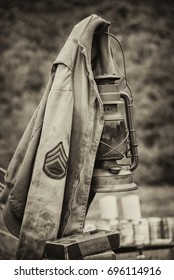 Vintage retro Sepia photograph of a US army sergeant jacket from WW2 hanging on a later in an upright vertical format