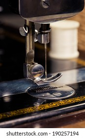 Vintage retro sewing machine with sewing equipment on a black background