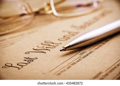 Vintage / retro style : Blue ballpoint pen, eye glasses and a last will and testament. A form is printed on a light brown mulberry paper and waiting to be filled and signed by testator / testatrix.