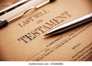 Vintage / retro style : Blue ballpoint pen and a last will and testament on a clip board. A form is printed on a light brown mulberry paper and waiting to be filled and signed by testator / testatrix.