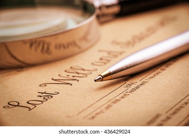Vintage / retro style : Blue ballpoint pen, a magnifier and a last will and testament. A form is printed on a light brown mulberry paper and waiting to be completed / signed by testator or testatrix.