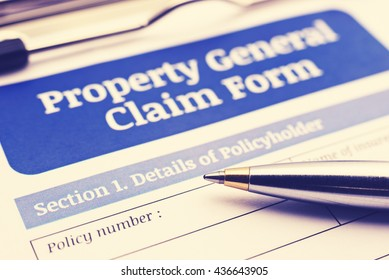 Vintage / retro style : Blue ballpoint pen on a property general claim form on a clipboard. A blank / empty form is waiting to be filled / completed and signed by a policy holder or an insured person.