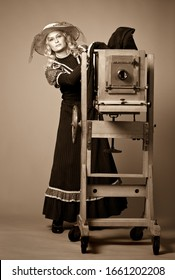 Vintage retro style photo of a young woman in a long modest dress and hat standing near a daguerreotype vintage camera on a gray background. Retro photography and vintage concept.