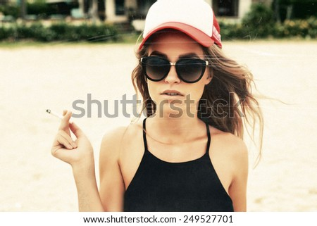 Vintage retro style textured with scratches and grain closeup outdoor summer fashion lifestyle portrait of pretty blonde woman in hat smoking cigarettes