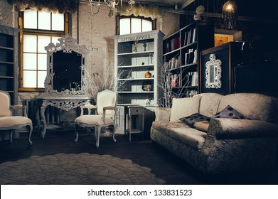 Vintage retro styled sitting living lounge room design interior. Cosy comfortable furniture elegant wealthy armchair and chair. Curved mirror cushions and pillows on couch sofa. Cupboards with books