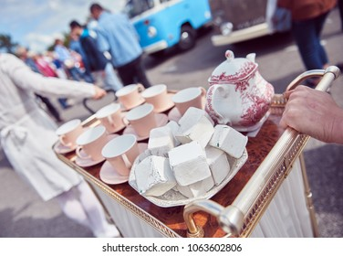 A vintage retro tea set, with giant sugar cubes in a fantasy world style. cup of tea on a summers day. photographed with a shallow depth of field.