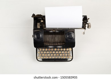 Vintage retro typewriter with sheet of paper on white wooden table background top view flat lay from above with copy space - journalism or writer concept