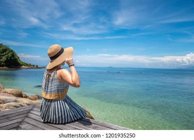 Vintage retro view of back beautiful Asian girl with long hair against the blue sea and horizon. Take vacation with lonely mood as concept.