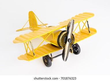 Vintage retro Yellow Metal propeller toy plane on white background studio shot for travel design and concept.