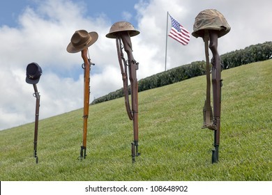 Vintage rifles and soldier's hats and helmets forming Fallen Soldier Battle Crosses, American Flag behind, left to right, eras of Civil War, Spanish American War, WWI, and WWII.