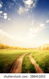 vintage road through fields with green grass and blue sky with clouds, natural background