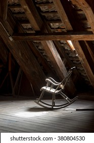Vintage rocking chair on deserted old attic floor. Grey rocking chair in the light. Delightful rocking chair at wooden attic. Closeup view of rocking chair, indoor photography