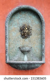 vintage roman head fountain on red wall