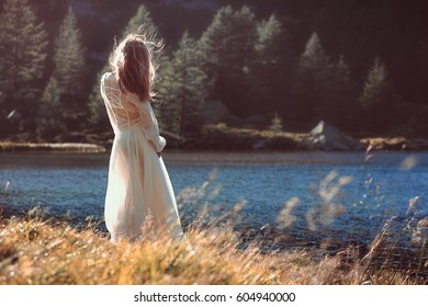 Vintage romantic woman touched by last rays of the sun