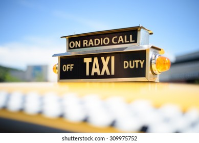 Vintage Roof Top Taxi Cab Sign on a Yellow Car.