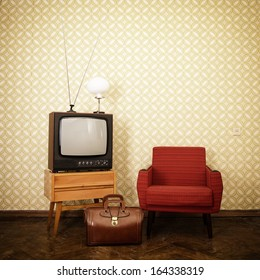 Vintage room with old fashioned armchair, retro tv, lamp and bag over obsolete wallpaper. Toned