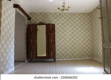 Vintage room in old house with wooden wardrobe and green patterns wallpaper. rural architecture