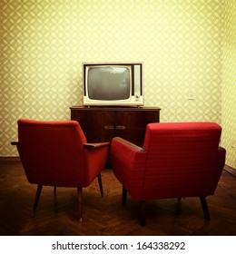 Vintage room with two old fashioned armchairs and retro tv over obsolete wallpaper. Toned