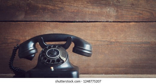 vintage rotary dial telephone on wooden board with copy space