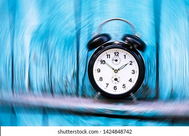 Vintage round shaped alarm clock with blurred motion. Time topic, Time travel Clock hands shown ten to two. Blue wooden wall with rickety boards on the background.
