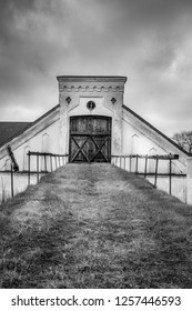 Vintage rural scene, dramatic front view of black and white old rustic worn stone barn farmhouse building with dark sky.