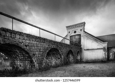 Vintage rural scene, dramatic front view of black and white old rustic worn stone barn farmhouse building with dark sky. Arched stone bridge in foreground.