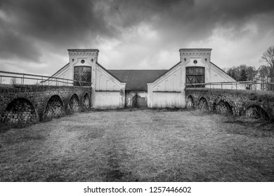 Vintage rural scene, dramatic front view of two black and white old rustic worn stone barn building farmhouse with dark sky. Two arched stone bridges in foreground.
