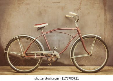 Vintage rusted cruiser bicycle on a wooden floor with a weathered background wall