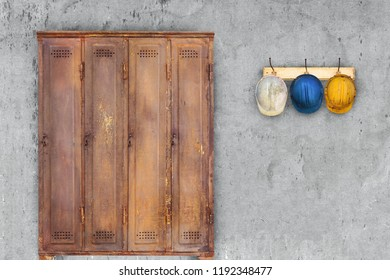 Vintage rusted locker and construction helmets hanging on a hat-rack in front of an old grey wall