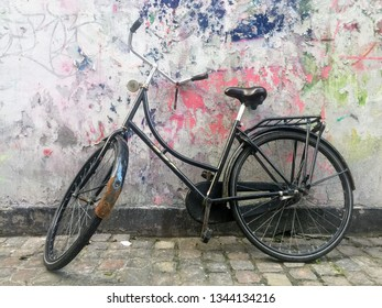 A vintage rustic bicycle leaning against a textured wall on a brick street in Copenhagen, Denmark.