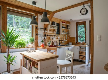Vintage rustic interior of kitchen with white furniture, wooden wall and rustical decor. Bright indoor with window. Cottage style.