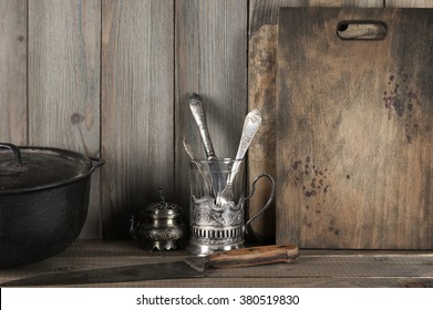 Vintage rustic kitchen still life: silver glass holder with cutlery, cast iron cauldron and cutting boards against vintage wooden background.