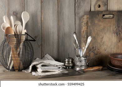 Vintage Rustic Kitchen Still Life: Silver Glass Holder With Cutlery, Wire  Basket With Wood