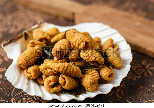 vintage rustic shot of traditional homemade kuih siput deep fried biscuit cookies in the shape of snails on a shell platter normally served during festivals likeramadhan and lunar chinese new year