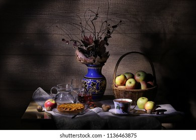 Vintage rustic still life : autumn leaves in a clay vase, basket of apples, pie, silver knife, antique tea cup, jar, glass of wine, hazelnuts, walnuts and chestnut on a table in light and shadows.