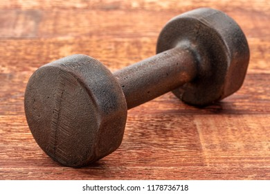 vintage rusty iron dumbbell on grained wood background - fitness concept