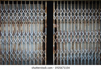 vintage rusty and old metal sliding grille door slightly opened showing darkness inside
