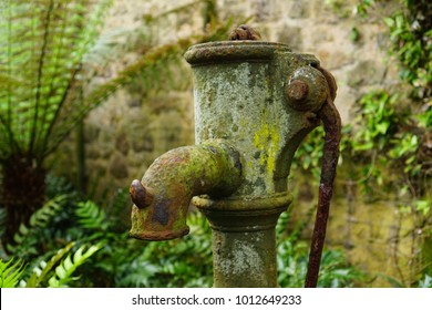 Vintage rusty water fountain hand pump in Tresco Abbey Garden, Isles of Scilly, England, UK