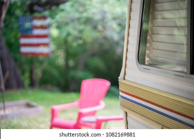 Vintage RV in a Texas camp ground with a red chair and American flag in the back ground.