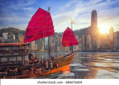 Vintage sail boat fron victoria port to Hongkong harbour for survice to tourist in Hong kong coty with sunset and blue sky, China, Travel asia and cityscape concept