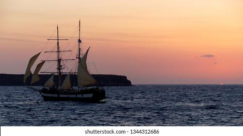 Vintage Sailboat sailing across an Ocean Sunset