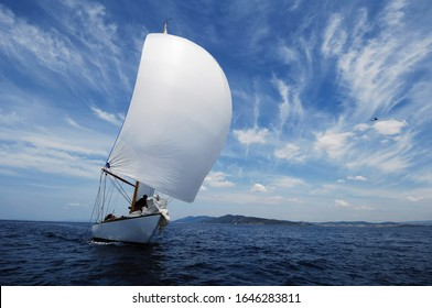 vintage sailboat with white spinnaker sailing downwind