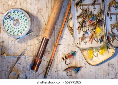 Vintage salmon flies, split cane fly fishing rod and reel on a rustic white wooden background