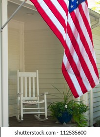 Vintage scene of rocking chair and US flag on front porch