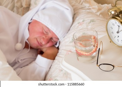Vintage scene of a sleeping man with his false teeth in a glass of water