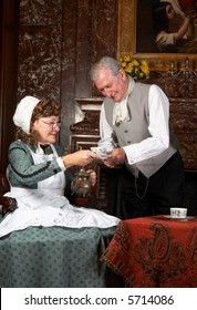 """Vintage scene of a victorian couple having tea. Shot in the antique castle """"Den Brandt"""" in Antwerp, Belgium (with signed property release for the Castle interiors)."""